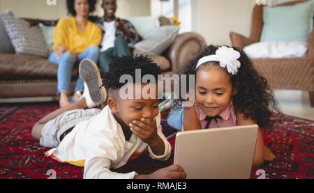 Cute African American Geschwister liegen auf dem Boden und Verwendung digitaler Tablet Stockfoto