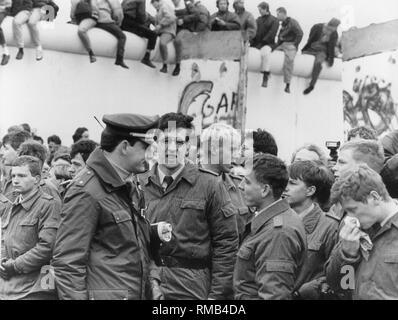 Eine West-Berliner Polizisten Gespräche mit seinen Ostdeutschen nach dem Fall der Berliner Mauer. - Stockfoto