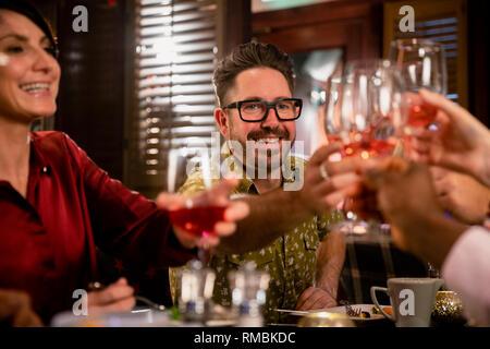 Fröhliche reifer Mann sein Glas für eine feierliche Toast mit ihren Freunden in einem Restaurant ein Essen sitzen. - Stockfoto