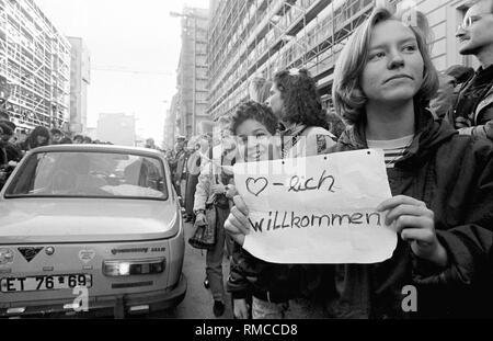 """Berlin, 10. November 1989: Zehntausende Ostberliner nehmen die Chance, einen Ausflug in den westlichen Teil der Stadt, nach der Öffnung der Grenze. Auf dem Foto ist ein Schüler von West Berlin am Grenzübergang """"Checkpoint Charlie"""". Die Ostberliner sind begeistert begrüßt. - Stockfoto"""
