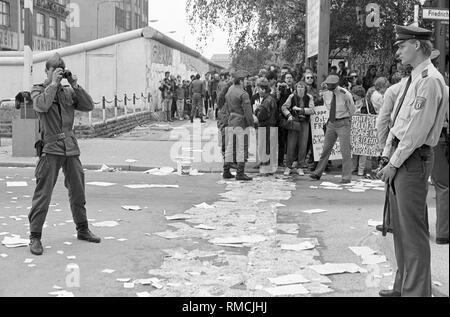 Die Gegner der 1987 Volkszählung stick Zehntausende Anmeldeformulare, die Berliner Mauer während einer spektakulären Kampagne am Grenzübergang Checkpoint Charlie, ein DDR-Grenzsoldaten Fotografien die Szene als die West-Berliner Polizei versucht, die Aktion zu stoppen. - Stockfoto
