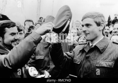 West-berliner Polizist und DDR-Grenzsoldaten Soldat in der Menge nach der Maueröffnung. Der Polizist Hände seine Kappe auf der borderman. - Stockfoto