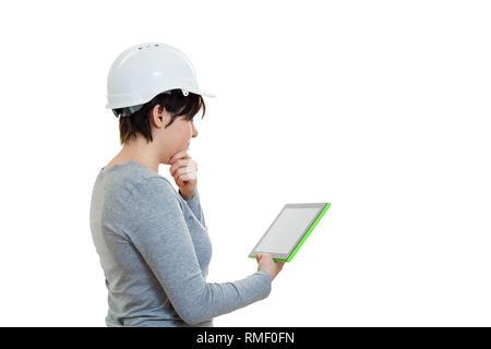 Seitenansicht nachdenklich der jungen Frau Ingenieur tragen Schutzhelm mit einem Tablet Computer Gadget auf weißem Hintergrund berechnen. - Stockfoto