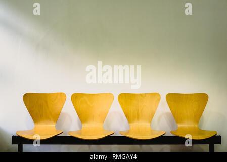 Wartezimmer mit leeren Stühle aus Holz, Konzept des Wartens und der Lauf der Zeit, freier Platz für Text. - Stockfoto