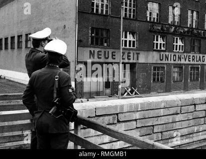 """Undatiertes Bild des Verlags Union-Verlag, der Herausgeber der """"Neuen Zeit"""" der Ost-CDU direkt an der Wand, im Vordergrund West-Berliner Polizisten. - Stockfoto"""