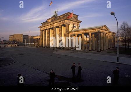 Tausende von Ost und West Berliner feiern die Öffnung der Grenze auf der Berliner Mauer am Brandenburger Tor. Ddr-Grenze wachen Menschen daran hindern, in den geschützten Bereich auf dem Platz vor dem Brandenburger Tor und den Pariser Platz. - Stockfoto