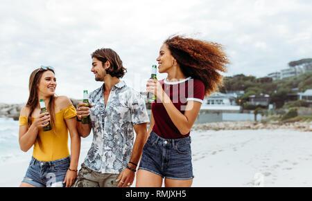 Gruppe von drei junge Freunde gehen im Freien mit Bierflaschen. Multi-ethnischen Freunde mit Bier zu Fuß am Strand entlang. - Stockfoto