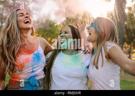 Drei Frauen Spaß Holi spielen mit Farben auf ihrem Gesicht spritzte. Freunde genießen Holi in einem Park und Lachen in der Freude. - Stockfoto