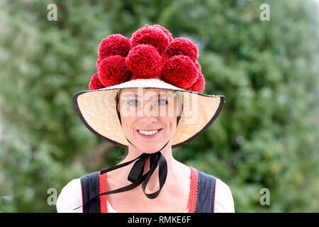 Attraktive junge Frau trägt eine traditionelle Schwarzwälder Bollenhut mit seinen 14 pompoms, wie sie in die Kamera im Freien gegen grün Lächeln - Stockfoto