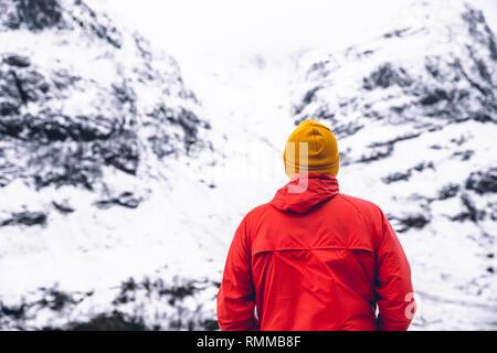 Mann, der durch die Berglandschaft im Winter schnee Glencoe Schottland - Stockfoto