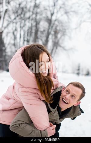 Ein glückliches Paar winter Reisende. Eine Frau reitet ein Mann im Winter verschneite Wald