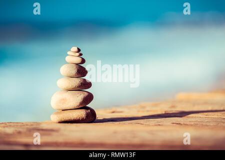 Nahaufnahme eines Kieselsteine Stapel auf der Brücke über den See, Wellness Steine, inneren Frieden und Leben in der Balance Konzept - Stockfoto