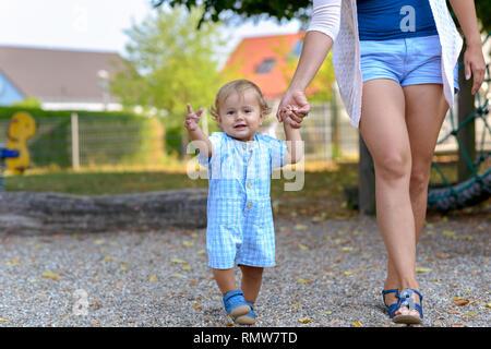 Happy Baby Boy zu Fuß mit seiner Mutter oder Babysitter im Freien auf einem Spielplatz in einem niedrigen Winkel Ansicht von ihm Winken in die Kamera - Stockfoto
