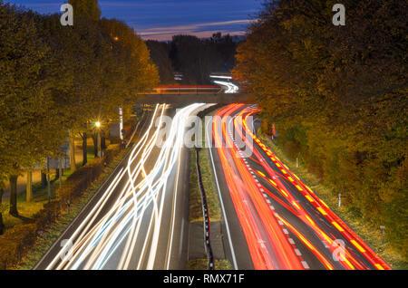 Lange Belichtung heller wegen des Verkehrs auf der Autobahn im Abendlicht fahren durch bewaldete Landschaft aus einem hohen Winkel auf einer Brücke gesehen - Stockfoto