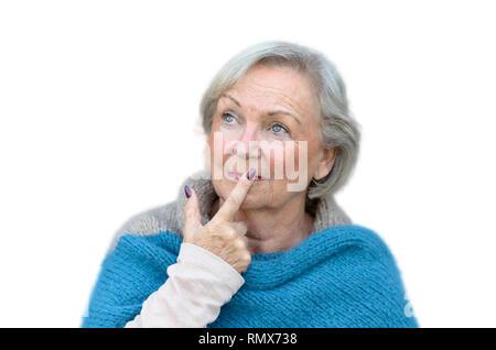 Nachdenklich stilvolle ältere Frau auf der Suche nach oben in die Luft mit ihrem Finger auf den Lippen und ein nachdenklicher Ausdruck gegen eine graue Wand - Stockfoto