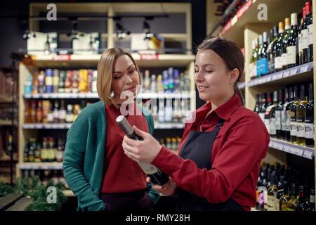 Foto der jungen Frauen mit einer Flasche Wein in der Hand - Stockfoto