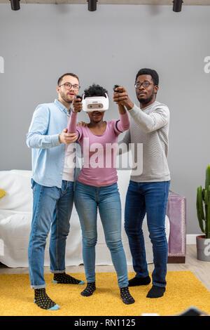 Afrikanischer junge Frau auf VR-Brille zum ersten Mal versuchen, und ihr Lächeln männliche Freunde zeigen ihr das Recht, so wie es in den Raum zu verwalten. - Stockfoto