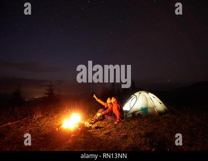 Nacht Camping in den Bergen. Junges Paar sitzt auf steilen Hügel vor der beleuchteten Zelt beleuchtet durch brennendes Feuer, junge Punkte an schöner Sternenhimmel zu Mädchen. Tourismus und die Schönheit der Natur. - Stockfoto