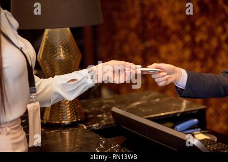 Business Frau mit weißen Abzeichen mockup zum Hotel anreisen, gibt Kreditkarte hotel Manager für Zimmer Reservierung, aus der Nähe. - Stockfoto
