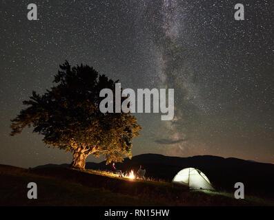 Junges Paar Wanderer genießen Nacht Camping in den Bergen. Rückansicht der Mann und die Frau sitzen auf Stühlen neben Lagerfeuer, beleuchtet touristische Zelt und großen Baum unter sternklarem Himmel voller Sterne und Milchstraße - Stockfoto