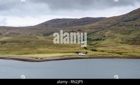 Eine traditionelle Ferienhaus liegt am Ufer des Meeres auf Scalpay, einer kleinen Insel neben Skye in den Highlands von Schottland. - Stockfoto