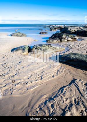 Kleine Bäche und Felsen erstellen Muster in den Sand von Longsands Strand in Tynemouth. - Stockfoto