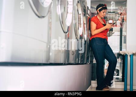 Junge Frau stehen und über Handy, während ihre Kleidung in einer Wäscherei service Shop in der Stadt - moderne Lifestyle zu beschäftigt für Bus gewaschen warten - Stockfoto