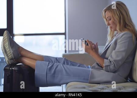 Mit Füßen auf Gepäck in Airport Lounge Geschäftsfrau - Stockfoto