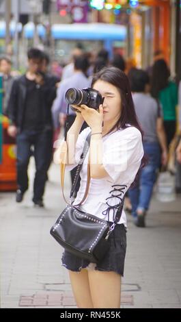 Junge asiatische Frau Touristen fotografieren auf der Straße in Hongkong. - Stockfoto