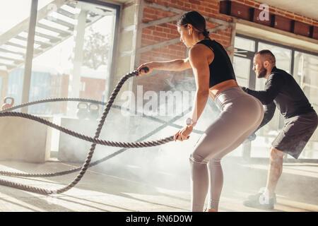 Kaukasische fit attraktive Paar in Sport Kleidung konzentrierte sich auf die Übung mit den Schlacht Seil, die eine verstärkte Anstrengung und Kraft, im Stand - Stockfoto