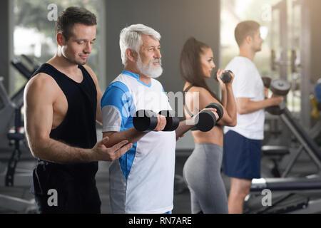 Horizontale Detailansicht von Mann und Frau auf tägliches Training in der Turnhalle. Junge sportlich attraktiven Mann zu helfen, einem anderen Mann gehen, Übungen mit Gewichten. Ältere Erwachsene im weißen T-Shirt zu trainieren. - Stockfoto