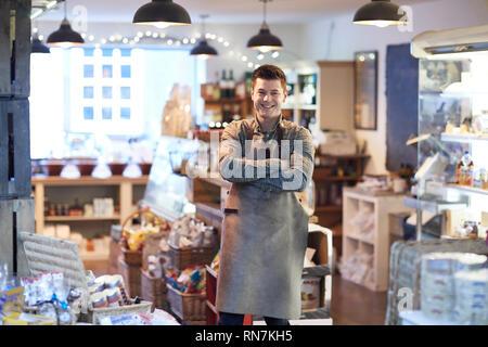 Portrait von lächelnden Mann Eigentümer von Feinkost Shop tragen Schürze - Stockfoto