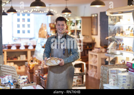 Portrait von lächelnden Mann Eigentümer von Feinkost Shop tragen Schürze Holding Laib Brot - Stockfoto