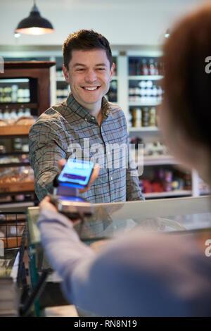 Männliche Kunden kontaktloses Bezahlen für das Einkaufen über Handy in Feinkost - Stockfoto