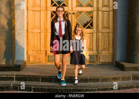 Outdoor Portrait von zwei Mädchen. Ein Schüler und eine Grundschule Schüler halten die Hände in der Nähe der Türen der Schule. - Stockfoto