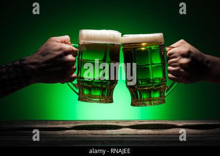 7/8-Ansicht von männlichen Freunden klirren mit Brille von Irish Ale auf st patricks day auf grünem Hintergrund - Stockfoto