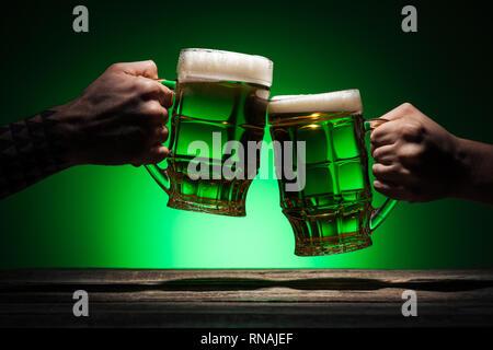 7/8-Ansicht von Freunden klirren mit Brille von Irish Ale auf grünem Hintergrund - Stockfoto