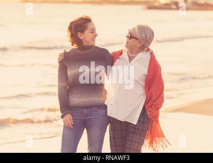 Portrait von Happy senior Mutter und erwachsene Tochter Ausgabe Zeit zusammen halten sich an den Händen zu lachen und zu Fuß am Strand bei Sonnenuntergang Licht in glückliche Familie