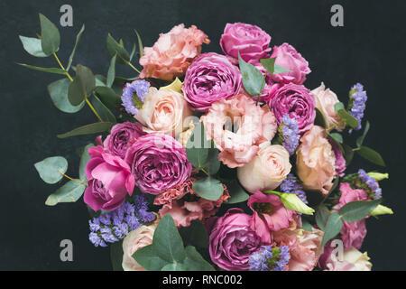 Blumenstrauß aus Rosen geschmückt mit Pfingstrosen und Eukalyptus. Hochzeit oder Geburtstag Blumen auf schwarzem Hintergrund - Stockfoto