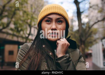 Porträt einer Frau im Winter Kleidung auf der Straße stehen. Asiatische Frau, die draußen im Winter tragen an einem kalten Morgen. - Stockfoto