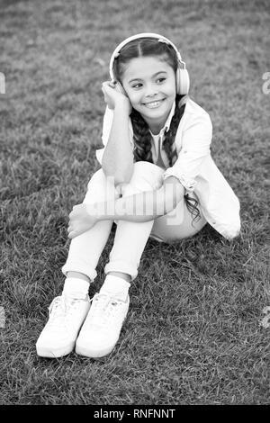 Positiven Einfluss der Musik. Kind Mädchen Musik moderne Ohrhörer. Kindheit und Jugend Musik Geschmack. Kleine Mädchen Musik hören Lieblingslied genießen. Mädchen mit Kopfhörer Natur Hintergrund.