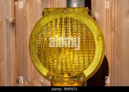 Gelbe Warnleuchte vor Holz- Hintergrund - Stockfoto