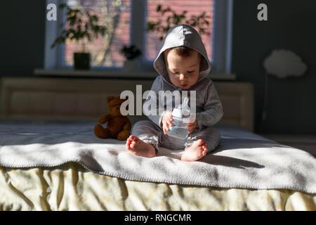 Baby Boy mit farbigen Pyramide Spielzeug auf Bett in seinem Zimmer - Stockfoto