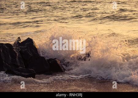 Wellen schlagen Rock bei Sonnenuntergang - Stockfoto