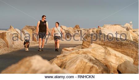 Ein junges Paar zu Fuß zu ihrem Hund entlang der Break-Wand neben dem Clarence River, zwischen grossen Felsbrocken, an einem Sommerabend in Yamba, Australien. - Stockfoto