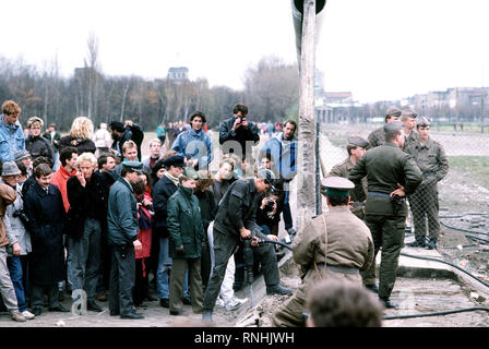 Eine Menschenmenge sammelt auf der westdeutschen Seite der Berliner Mauer am Potsdamer Platz zu sehen, wie sich die Struktur wird demontiert. - Stockfoto