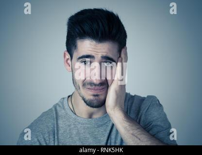 Close up Portrait von Stattlichen verzweifelte junge Menschen leiden an Depressionen miserabel, melancholisch und traurig auf neutralem Hintergrund isoliert. In P - Stockfoto
