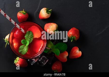 Erdbeersaft und Pfefferminze oben und frische Erdbeeren auf den schwarzen Stein, Ansicht von oben und im Sommer Getränke Konzept