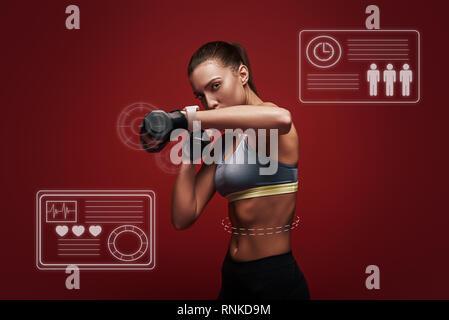 Porträt einer selbstbewussten jungen Frau fitness Übungen mit Hanteln über den roten Hintergrund. Studio shot - Stockfoto