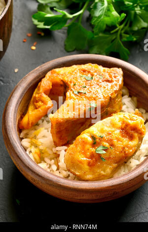 Nahaufnahme von Fisch Curry mit Reis in Houten auf schwarz Tisch aus Stein. Indische Küche. - Stockfoto